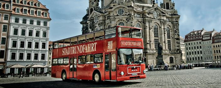 Photo of a red double-decker bus in front of the Frauenkirche
