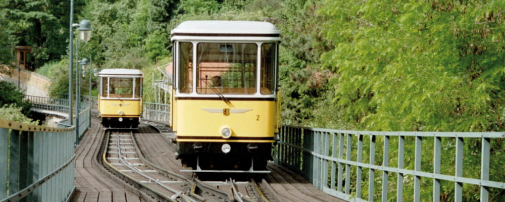 The photo shows two Standseilbahn cars meeting at the passing loop