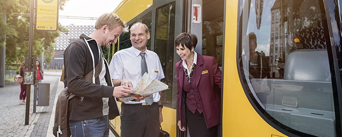 Photo of DVB staff explaining the way to a passenger with a map