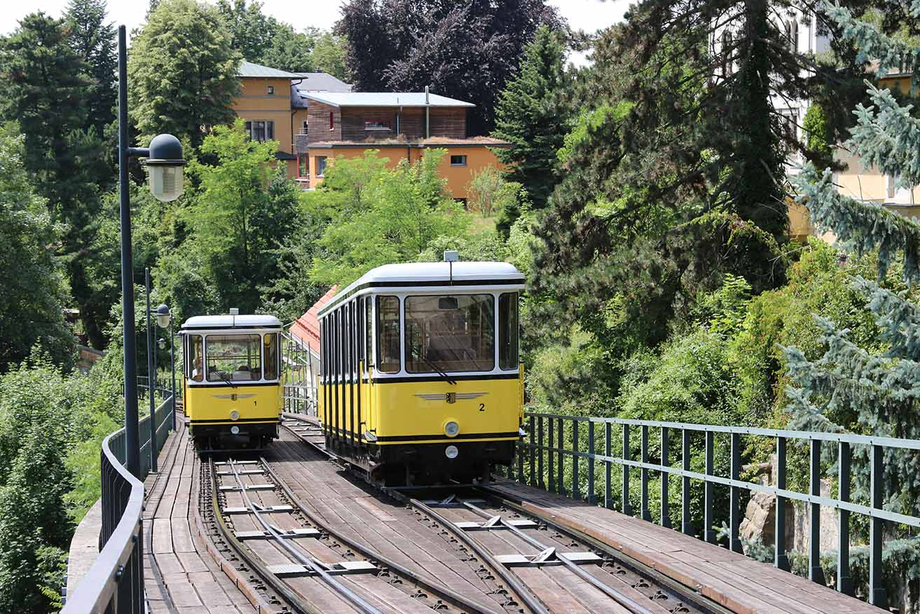 Photo of two hillside railway cars moving alongside one another on tracks