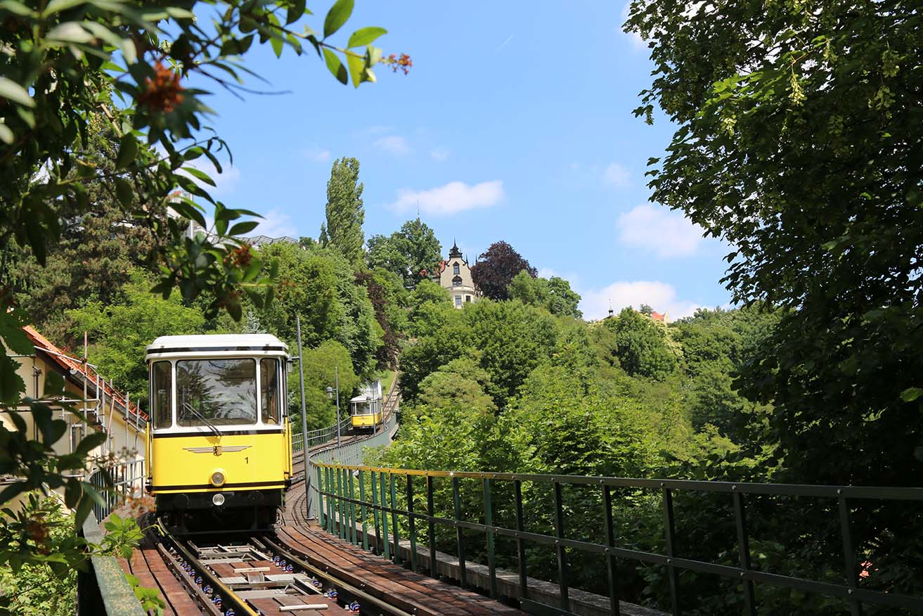 Photo of two hillside railway cars driving behind one another on tracks
