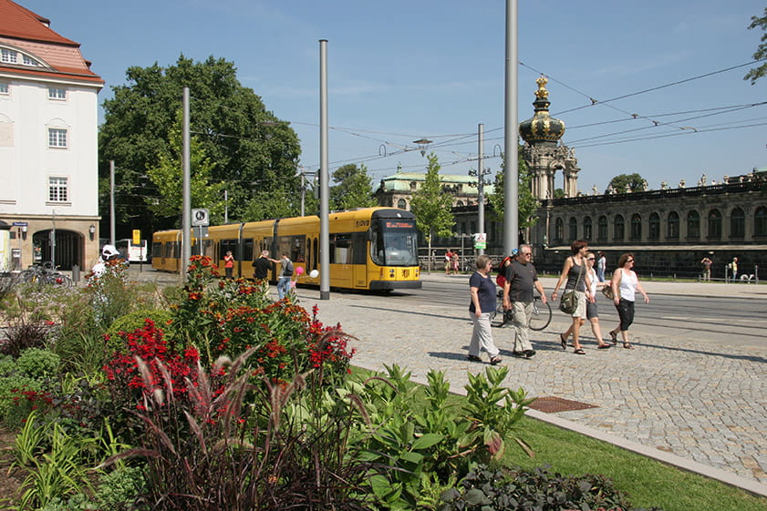Yellow tram and Zwinger in the background; planted areas of Postplatz in the foreground