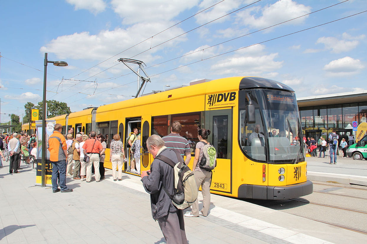 Stop with people and a yellow tram in front of Messe Dresden trade fair glass façade