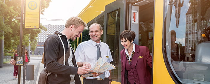 The photo shows two transport service staff helping a passenger with a map, a friendly smile on their lips.