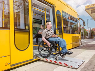Photo of a wheelchair user exiting a tram on a ramp
