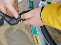 Photo of two hands opening a bike lock