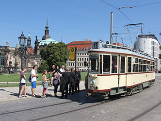 The photo shows a historical tram opposite Dresden Zwinger.