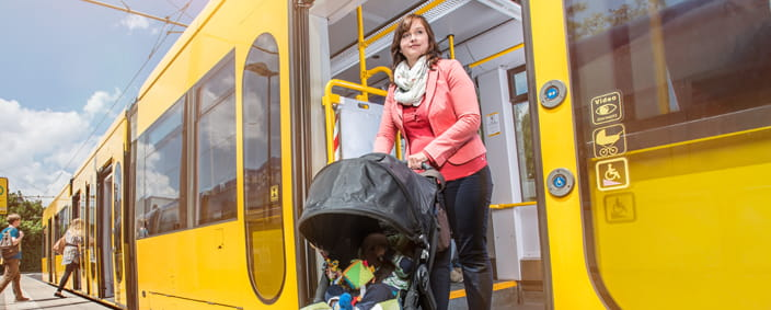 Photo of a woman with a pushchair getting out of a tram