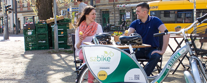 Photo of a woman and a man sitting at a café table. An sz-bike in the foreground