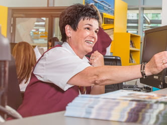 The photo shows a customer service employee at a ticket counter