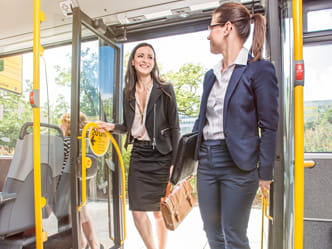 The photo shows two businesswomen getting on a bus.