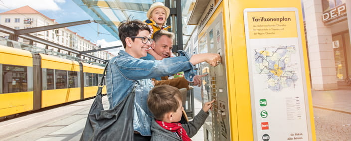 The photo shows a family standing in front of a ticket machine, buying a ticket.