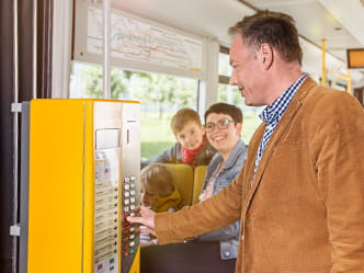 The photo shows a passenger buying a ticket from a machine on a tram.