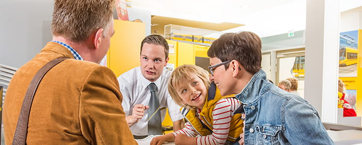The photo shows a family in conversation with a customer service employee
