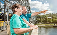 The photo shows a couple standing on the Blue Wonder bridge looking at the Elbe.